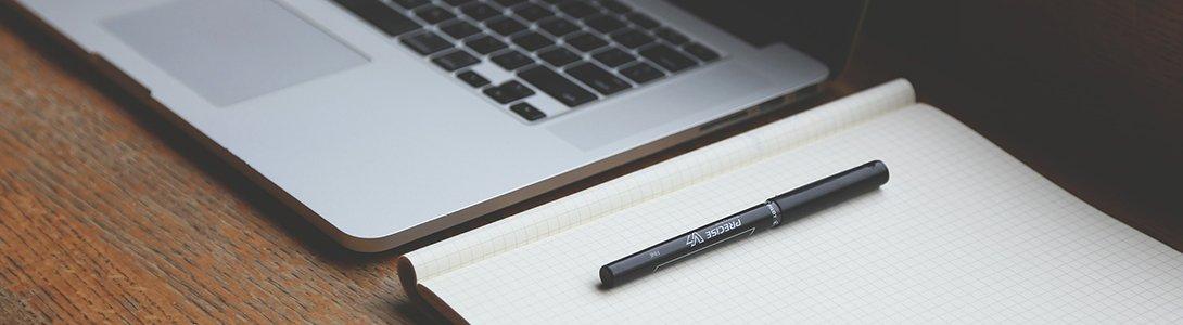 Laptop und Papierblock auf Schreibtisch